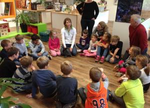 Kinder sitzen im Kreis mit uns am Boden